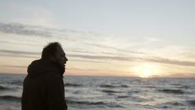 Junger Mann, der in das Ufer des Meeres allein geht und auf den Wellen schaut Mann, der den Sonnenuntergang auf dem Strand genieß stock video