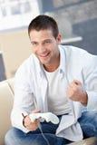 Junger Mann, der das Videospiellächeln genießt stockfoto