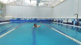 Junger Mann, der das vordere Schleichen in einem Pool schwimmt stock video