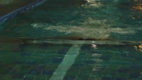 Junger Mann, der das vordere Schleichen in einem Pool schwimmt Dynamischer und geeigneter Schwimmer, der den Schmetterlingsanschl stock footage