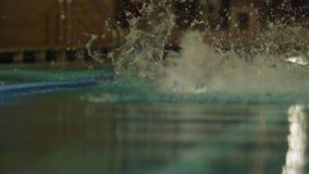 Junger Mann, der das vordere Schleichen in einem Pool schwimmt Dynamischer und geeigneter Schwimmer, der den Schmetterlingsanschl stock video