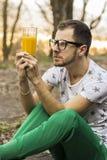 Junger Mann, der dem Glas mit Saft verwechselt betrachtet stockbilder