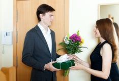 Junger Mann, der dem Mädchen Geschenke gibt Lizenzfreies Stockbild