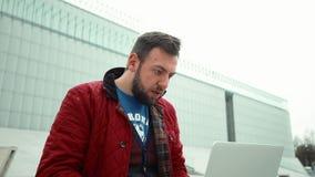 Junger Mann, der an dem modernen Notizbuch im Freien arbeitet stock footage