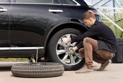 Junger Mann, der den durchbohrten Reifen auf seinem Auto ändert lizenzfreie stockfotografie