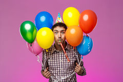 Junger Mann, der den Geburtstag, bunte baloons über purpurrotem Hintergrund halten feiert lizenzfreie stockfotos
