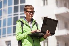 Junger Mann, der den Laptop geht in der Stadtstraße verwendet Stockfotos