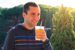 Junger Mann, der den Orangensaft im Freien trinkt Stockbild
