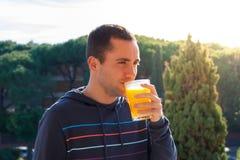 Junger Mann, der den Orangensaft im Freien trinkt Lizenzfreie Stockfotografie