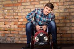 Junger Mann, der den Spaß reitet einen Spielzeuglastwagen hat Lizenzfreies Stockbild