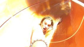 Junger Mann, der den Spaß reitet hinunter das Rohr an einem Wasserpark hat stock video footage