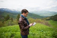 Junger Mann, der den Tabletten-PC auf die Oberseite des Berges berührt Lizenzfreie Stockfotos