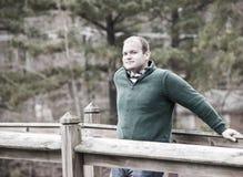 Junger Mann, der an der Brückenschiene sich lehnt Stockbilder