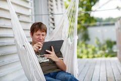Junger Mann, der in der Hängematte sich entspannt und Tablet-Computer verwendet Stockbilder