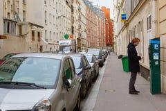 Junger Mann, der an der Parkuhr in Paris zahlt Stockbild