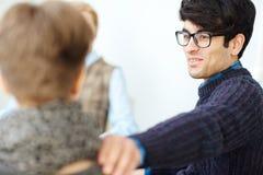 Junger Mann, der in der Sitzung lächelt stockbilder