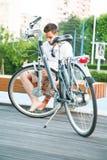 Junger Mann, der in der Stadt mit Fahrrad stillsteht Stockfotografie