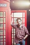 Junger Mann, der an der Telefonzelle steht Stockfotografie