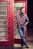 Junger Mann, der an der Telefonzelle steht Lizenzfreie Stockfotografie