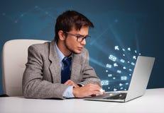 Junger Mann, der an DEST sitzt und auf Laptop mit Mitteilungsikone schreibt Lizenzfreie Stockbilder