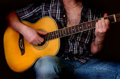 Junger Mann, der die Akustikgitarre - lokalisiert auf Schwarzem spielt Lizenzfreie Stockfotografie