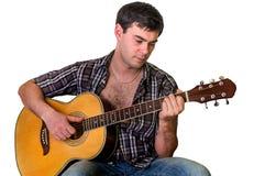 Junger Mann, der die Akustikgitarre - lokalisiert auf Weiß spielt Lizenzfreies Stockbild