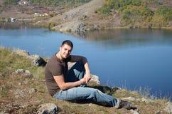 Junger Mann, der die Ansicht von einem schönen See genießt Lizenzfreies Stockbild