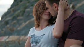Junger Mann, der die Frau draußen sitzt auf Küste am Sommertag umarmt stock footage