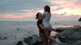 Junger Mann, der die Frau, stehend auf Strand auf dem Sommer draußen glättend hält stock video footage