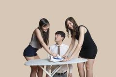 Junger Mann, der die glücklichen Frauen bügeln Bindung über farbigem Hintergrund betrachtet Lizenzfreie Stockbilder