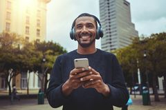 Junger Mann, der die Musik auf Kopfhörer durch Handy genießt stockbilder