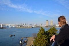 Junger Mann, der die Regenbogen-Brücke in Tokyo-Stadt betrachtet japan Stockbild