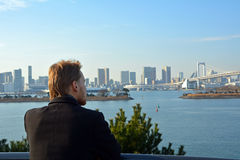 Junger Mann, der die Regenbogen-Brücke in Tokyo-Stadt betrachtet japan Lizenzfreie Stockfotos