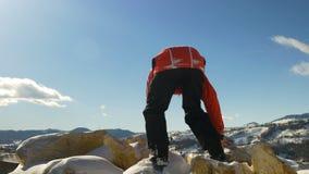 Junger Mann, der die Spitze eines Berges sich fühlt glücklich für seinen Erfolg klettert stock video