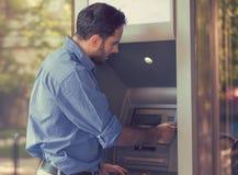 Junger Mann, der draußen ATM verwendet lizenzfreies stockbild