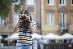 Junger Mann, der draußen durch Weinlesekamera fotografiert Lizenzfreies Stockbild