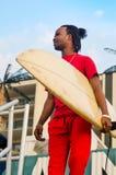 Junger Mann, der draußen ein Surfbrett hält lizenzfreie stockbilder