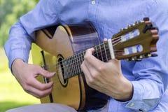 Junger Mann, der draußen eine klassische Gitarre spielt Stockbild