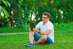 Junger Mann, der draußen eine Notenauflage verwendet Lizenzfreie Stockfotos