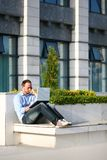 Junger Mann, der draußen an Laptop arbeitet Lizenzfreie Stockfotografie