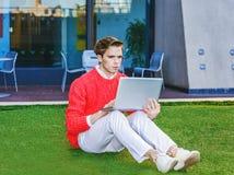 Junger Mann, der draußen an Laptop-Computer arbeitet Stockfotografie