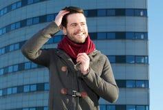 Junger Mann, der draußen mit der Hand im Haar lächelt Lizenzfreie Stockfotografie