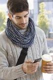 Junger Mann, der draußen Mobile verwendet Stockbild