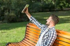 Junger Mann, der draußen selfies auf der Bank macht Stockbilder