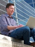 Junger Mann, der draußen am Laptop lächelt Lizenzfreie Stockbilder
