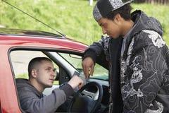 Junger Mann, der Drogen vom Auto behandelt Stockfoto