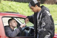Junger Mann, der Drogen vom Auto behandelt Lizenzfreie Stockfotos