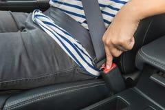 Junger Mann, der Druckknopf auf Schnalle bedrängt, um Sicherheitsgurt freizugeben lizenzfreies stockbild