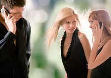Junger Mann, der durch den Handy und zwei Frauen betrachten ihn spricht Stockbild