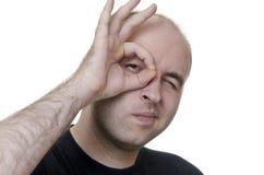 Junger Mann, der durch Finger auf weißem Hintergrund schaut Lizenzfreies Stockfoto